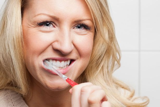 Woman-brushing-teeth-in-bathroom